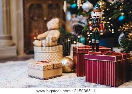 Picture of decorated Christmas or New Year tree with many gifts against home interior. Handmade present and many boxes under fir tree. Seasonal holidays. Winter, holidays concept