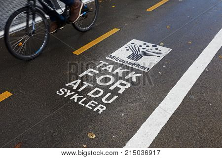 Trondheim Norway - October 16 2017: One bicycle passing a sign on the bicycle track with a message fromm the Tronheim enviroment project Miljopakken with text in Norwegian translated to English reading Thanks for cycling.