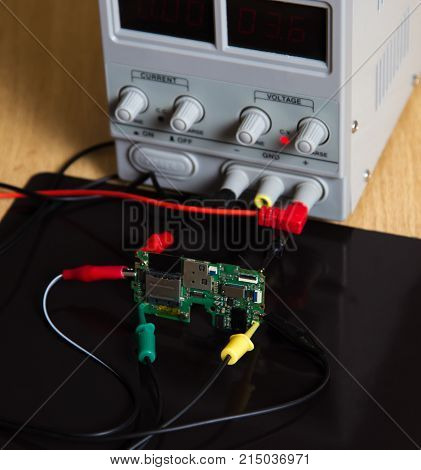 probe of oscilloscope card chips power supply with wire clamps on wooden table. Repair electronic circuit board probes measuring device