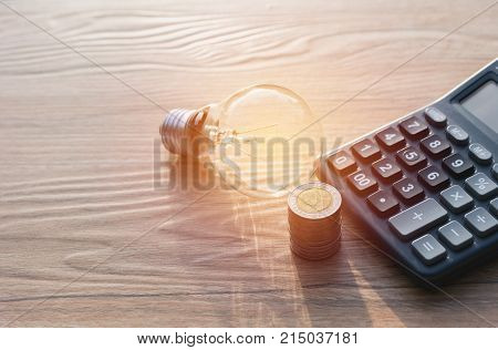 Energy saving light bulb with stacks of coins and calculator for financial accounting and saving concept.
