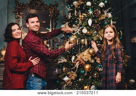 Friendly family of father, mother and daughter decorates New Year tree, being glad to have coming winter holidays, enjoy domestic atmosphere. Family of three members being busy with decorations
