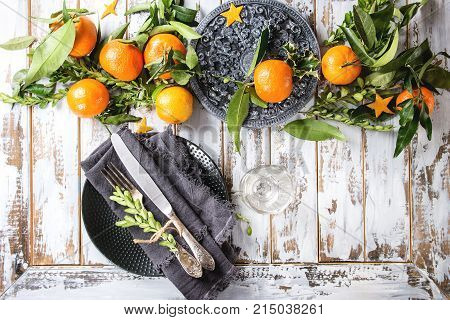 Christmas table decorations with clementines or tangerines with leaves and green branches on black ornate board. Empty plate with cutlery and textile napkin over white wooden plank table. Top view