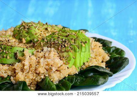 Easy quinoa, avocado and fresh spinach salad with spices. Blue background. Healthy quinoa avocado breakfast idea. Closeup