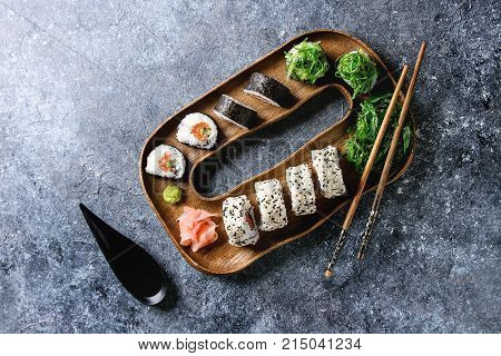 Homemade sushi rolls set with salmon, sesame seeds serving in wooden plate with pink pickled ginger, soy sauce, wasabi, seaweed salad, chopsticks on gray texture background. Top view, space