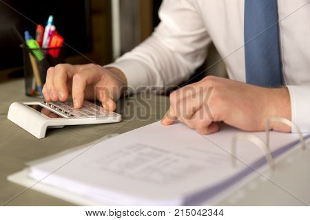 Successful business working overtime and calculating balance sheet.