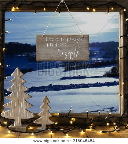 Sign With English Quote There Is Always A Reason To Smile. Window Frame With Winter Landscape With Snow. View To Snowy Scenery Outside. Christmas Tree And Fairy Lights.