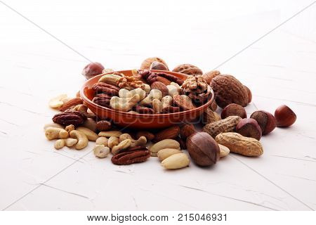bowl with mixed nuts on white background. Healthy food and snack. Walnut pecan almonds hazelnuts and cashews