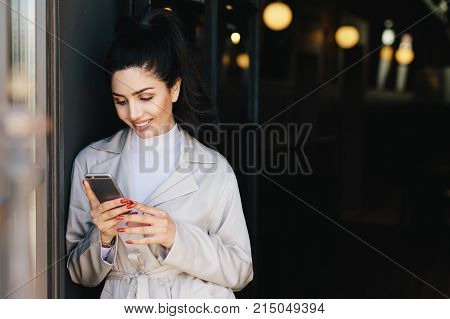 Fashionable beautiful woman with dark hair tied in pony tail dressed in white elegant coat holding cell phone looking into screen with delightful expression. Young pretty model communicating online