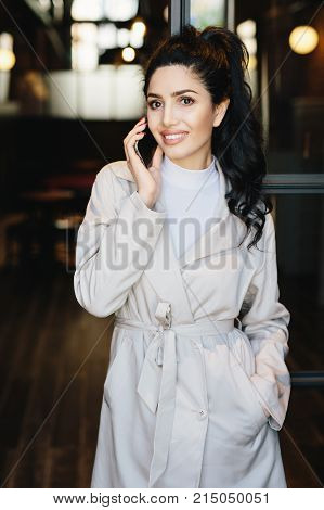 Vertical portrait of elegant brunette businesswoman in white coat communicating over cell phone while standing outdoors. Caucasian woman with beautiful appearance using modern gadget. Fashion concept
