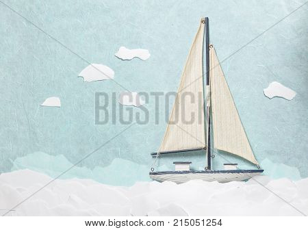 Wooden Sailboat Model on light blue background with sea made from paper. Yacht model with clouds made from papers shoot from above