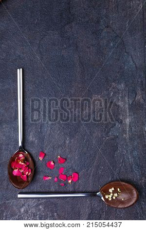 Melted and frozen chocolate on spoons with flowers and sticks beside on a stone background. Spoons make a right angle