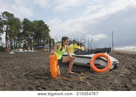 Girl lifeguard on duty keeping a buoy at the beach. Water scooter Lifeguard rescue equipment orange preserver tool on beach. Safety rescue vacation