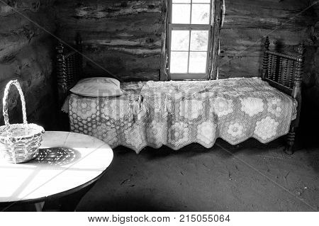 Wooden bedframe with pillow and quilt in second bedroom of early settler's old log cabin with dirt floor