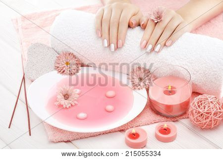 beautiful pinc manicure with candles, chrysanthemum flower and towel on the white wooden table. spa