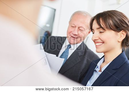Trainee and senior citizen in dialogue during business meeting