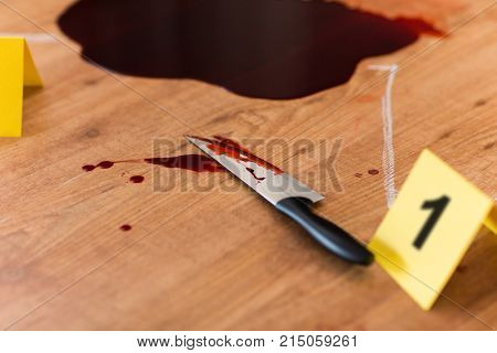 murder, kill and forensic evidence concept - knife in blood lying on floor near chalk outline of body at crime scene