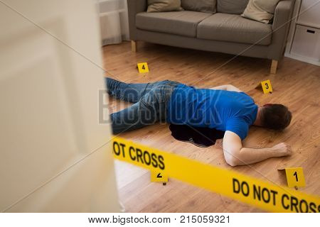 murder, kill and people concept - dead man body in blood lying on floor and bullet sleeves fenced by police tape at crime scene at home room