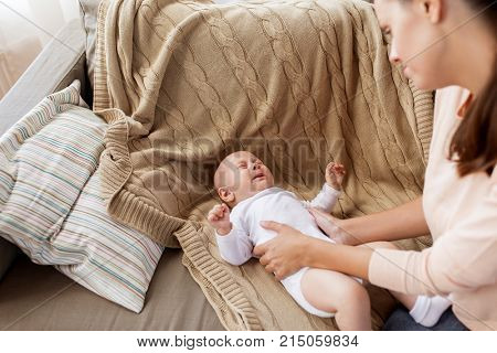 family, motherhood and people concept - mother soothing crying little baby boy at home