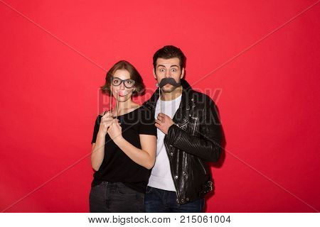 Playful punk couple posing with fake mustache, lips and eyeglasses while looking at the camera over red background