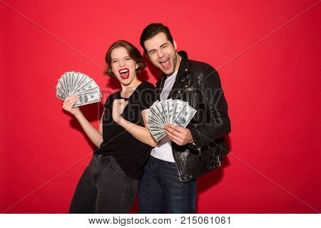 Cheerful screaming punk couple holding money and looking at the camera over red background