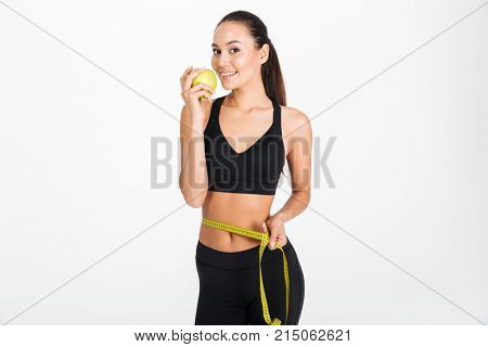 Portrait of a healthy asian fitness woman holding apple and measuring tape around her waist isolated over white background