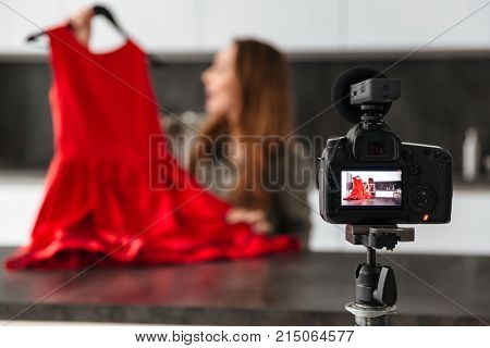 Pretty young girl recording her video blog episode about new red cocktail dress shoes while sitting at the kitchen table at home