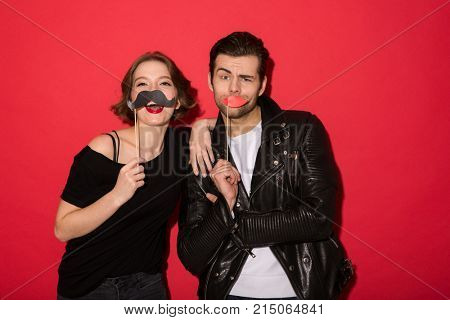 Funny cheerful punk couple posing with fake mustache and lips while looking at the camera over red background