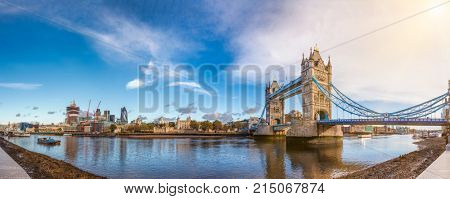Panoramic London skyline with iconic symbol, Tower Bridge and Her Majesty's Royal Palace and Fortress, known as the Tower of London as viewed from South Bank of the River Thames in the morning light