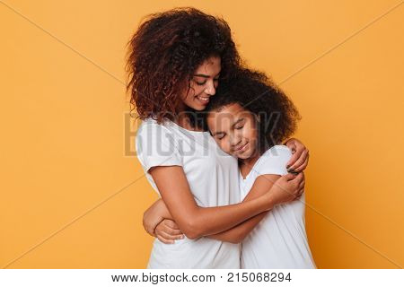 Portrait of two lovely african sisters hugging isolated over orange background