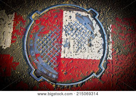 Red white sewer hatch with rubbed paint close up