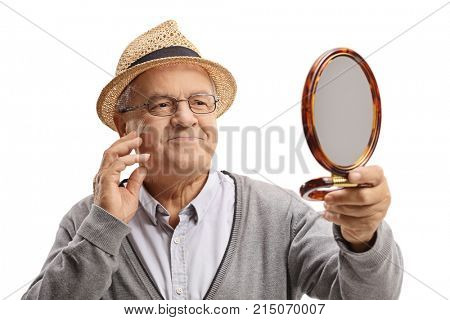 Elderly man looking at himself in a mirror and touching his face isolated on white background