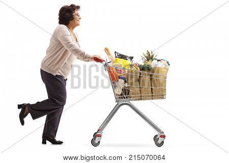 Full length profile shot of a mature woman running and pushing a shopping cart filled with groceries isolated on white background