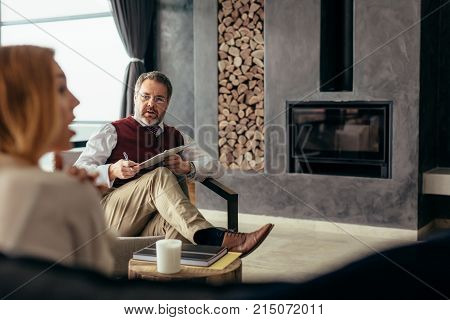 Relationship consultant giving advice to couple at home. Family psychologist consulting couple in trouble.