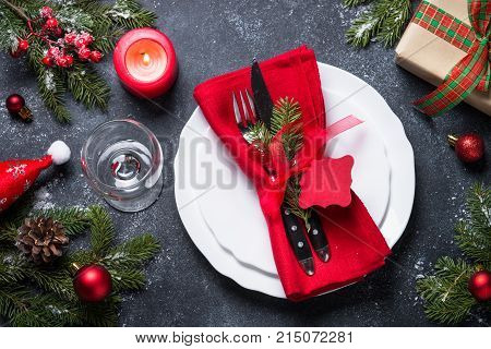 Christmas table setting - plate cutlery wineglass with christmas decorations on black stone table. Top view.