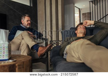 Stressed man listening psychologist's analysis. Male patient lying on sofa during psychotherapy session.