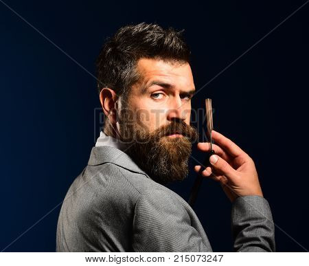 Man With Long Beard Holds Blade For Razor. Barbershop Advertising