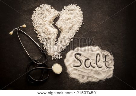 Sprinkle salt on dark background with broken heart shape made from salt. Unhealthy addition for meal, concept of healthy lifestyle.