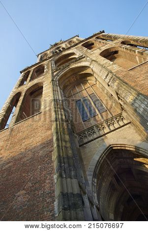 Vertical close up view on brown brick old antique church bell tower. Classic Europe European church cathedral bell tower. Classic brick church architecture in Utrecht city Holland