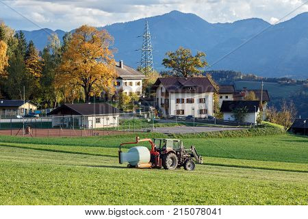 Tractor hay bale wrapper, picking up and applying plastic cling wrap to a round bale. Village Obermillstatt, Carinthia, Austria