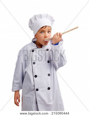 Little cook in white uniform and a cap trying something with a wooden spoon on a white isolated background