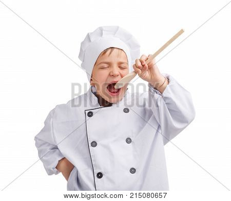 A small cook with closed eyes in a white uniform and a cap raised a spoon to an open mouth on a white isolated background