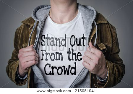 Man showing Stand Out From The Crowd tittle on t-shirt. Talent and uniqueness concept.
