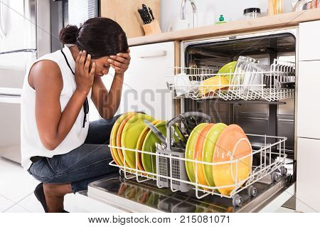 Sad African Woman Crouching Near Dishwasher In Kitchen