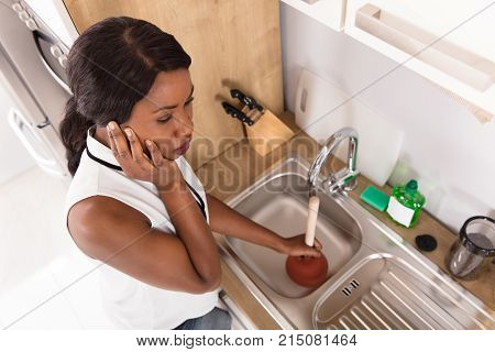 Elevated View Of A Young Unhappy African Woman Using Plunger In Clogged Sink