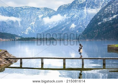 Girl walking on a deck over an alpine lake - Travel destination theme image with a woman walking on a narrow deck that crosses the Hallstatter lake surrounded by the Austrian Alps mountains.