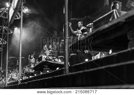 VARANASI INDIA - MARCH 14 2016: Black and white picture of unidentified Hindu indian men praying at religious Ganga Aarti ritual at Dashashwamedh Ghat in Varanasi India.