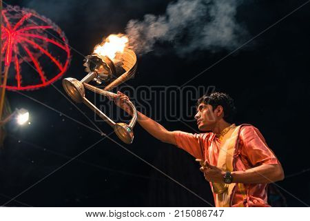 VARANASI INDIA - MARCH 14 2016: Horizontal picture of ornated candle on the hand of hindu indian ma at religious Ganga Aarti ritual at Dashashwamedh Ghat in Varanasi India.