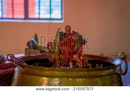 KATHMANDU, NEPAL - SEPTEMBER 04, 2017: Unidentified people inside of a building giving an oblation food and flowers to their goods, golden figures and praying near of Bindabasini temple, is of great religious importance to local Hindus.