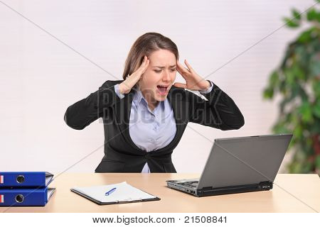 A nervous young businesswoman yelling to a laptop in the office
