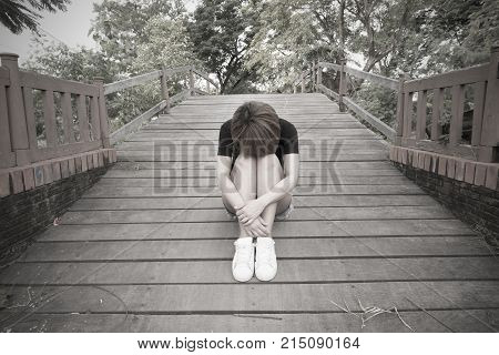 Sad woman, lonely, sitting hugging his knees, in a lonely atmosphere.